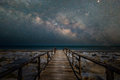 Wooden bridge walkway to the beach with milky way galaxy Royalty Free Stock Photo