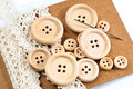Wooden buttons, a needle and white lace on a brown carton Royalty Free Stock Image