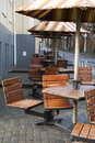 Wooden cafe chairs, tables and umbrellas Royalty Free Stock Photos