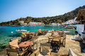 Wooden cafe tables at pier of Loutro town on Crete island, Greece Royalty Free Stock Photo