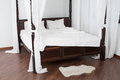 Wooden canopy bed and a white hide on the floor in light room Stock Photos