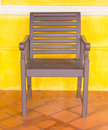 Wooden chair on yellow wall. Royalty Free Stock Photo