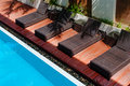 Wooden chairs beside the pool swimming Stock Photos
