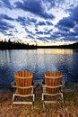 Wooden chairs at sunset on lake shore landscape with adirondack of relaxing in algonquin park canada Royalty Free Stock Images