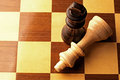Wooden chess pieces on a chessboard close up overhead view of two with the lighter piece lying its side and the black king Stock Photos