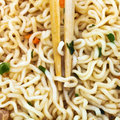 Wooden chopsticks on cooked instant ramen close up Stock Image