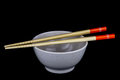 Wooden Chopsticks with Food Bowl on Black Background Royalty Free Stock Photo