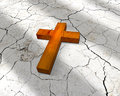 Wooden chrisitian cross d lying on cracks Stock Photography