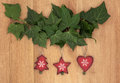 Wooden christmas decorations old fashioned hanging from ivy leaf sprigs over oak background Stock Image