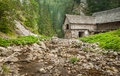 Wooden cottage in the mountains with creek and grass Royalty Free Stock Images