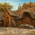 Wooden cottage with roses old and a thatched roof Stock Image