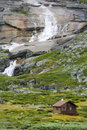 Wooden cottage with waterfall in wild nature Stock Photos