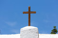 Wooden cross crucifix on a white church against a blue sky in spain Royalty Free Stock Image