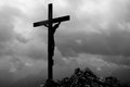 Wooden cross on mountain summit with jesus statue peak Royalty Free Stock Images