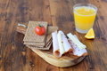Wooden cutting board with crispbread, cheese, ham, cherry tomato, glass of fresh orange juice on a wooden background Royalty Free Stock Photo