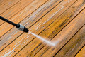 Wooden deck floor cleaning with high pressure water jet. Royalty Free Stock Photo