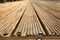 A wooden deck floor in the sunlight diminishing pespective Royalty Free Stock Images