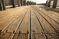 A wooden deck footpath in the sunlight diminishing pespective Stock Image
