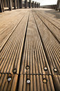 A wooden deck footpath in the sunlight diminishing pespective Royalty Free Stock Images
