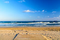Wooden deck over sandy beach with blue sky and ocean on background. White foam on top of the ocean waves in Tarragona Spain Royalty Free Stock Photo
