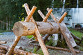 Wooden device for cutting firewood and the stack of wooden logs near the wooden fence Royalty Free Stock Photo