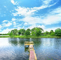Wooden dock pier on a lake in summer sunny day Stock Image