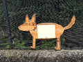 Wooden dog (fox) contour flat sign on the metal ne