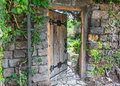 Wooden door decorated with iron forging, slightly open. Wall of