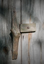 Wooden door handle on a barn door carved branch serves as an old dappled sunlight casts soft shadows the weathered wood of the Royalty Free Stock Photography
