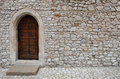 A wooden door with pointed gothic style arch in a stone wall Royalty Free Stock Photo