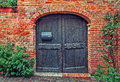 Wooden door and red brick wall. Royalty Free Stock Photo