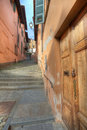 Wooden door and small paved street in Saluzzo. Royalty Free Stock Photo