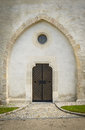 Wooden door and small window to stony church Stock Photo