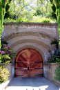Wooden door under a cement archway in a garden Royalty Free Stock Photo
