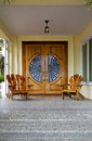Wooden doors and chairs decorative create a welcome entrance to a home Stock Photo