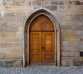 A wooden double door with pointed gothic arch in a wall made of stone blocks Royalty Free Stock Photo