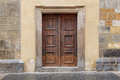 A wooden double door with rectangle door frame in a stone wall Royalty Free Stock Photo