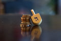 Wooden Dreidel Resting on Stack of Coins Royalty Free Stock Photo