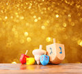 Wooden dreidels for hanukkah and glitter golden lights background Royalty Free Stock Photo