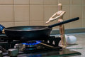 Wooden dummy, mannequin or man figurine cooking at Royalty Free Stock Photo