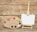 Wooden easel with clean paper and artist color palette Stock Images