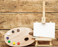 Wooden easel with clean paper and artist color palette Royalty Free Stock Image