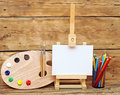 Wooden easel with clean paper and artistic equipment Stock Image