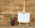 Wooden easel with clean paper and colorful pencils Stock Images