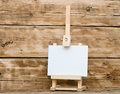 Wooden easel with clean paper on old table Stock Photo