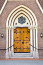 Wooden entrance door of church decorative with fittings in arch shaped wall recess Stock Image