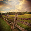 Wooden fence with clouds in country background an old rustic is a grass filed trees and the for a or nature concept Stock Photography