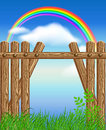 Wooden fence on green grass and rainbow Royalty Free Stock Photo