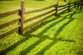 Wooden fence on green meadow Royalty Free Stock Photo