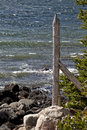 Wooden fence post with barbed wire on rocky shore rustic of coast Stock Photography